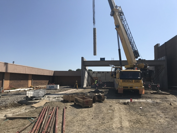 A precast panel is moved into place to create the PHS cafeteria/storm shelter.